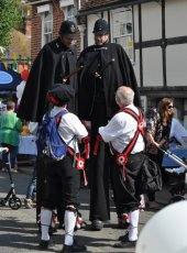 The Morris Men talking to the long leg of the Law!